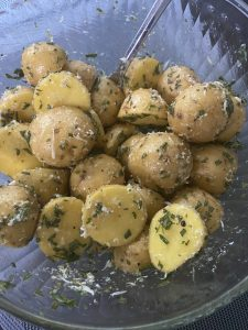 baby potatoes with olive oil, herbs, and parmesan cheese in a bowl