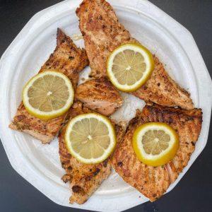 plated lemon garlic salmon with lemon wedges as a garnish